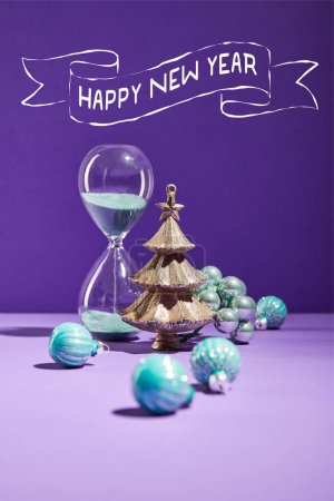 selective focus of decorative Christmas near blue baubles and hourglass on purple background with happy new year lettering
