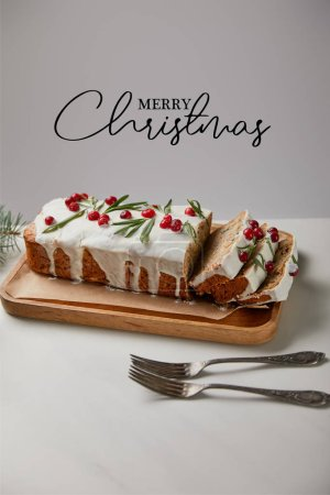 Photo for Traditional Christmas cake with cranberry near forks on white table isolated on grey with Merry Christmas illustration - Royalty Free Image