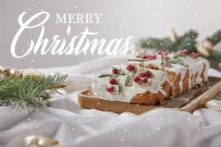 selective focus of traditional Christmas cake with cranberry on wooden board near baubles and pine needles isolated on grey with Merry Christmas illustration