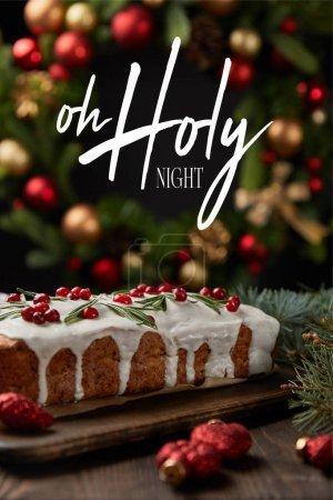 Photo pour L'accent sélectif du gâteau de Noël traditionnel avec canneberge près de la couronne de Noël avec baubles sur table en bois avec illustration de la nuit sainte - image libre de droit
