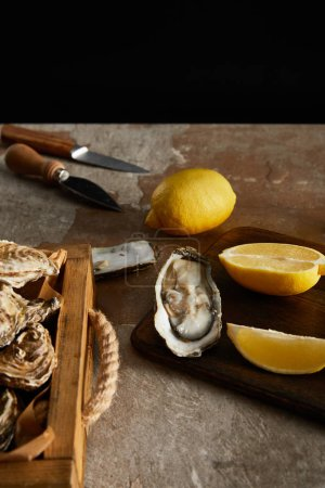Photo for Selective focus of delicious oysters near lemons and knifes isolated on black - Royalty Free Image