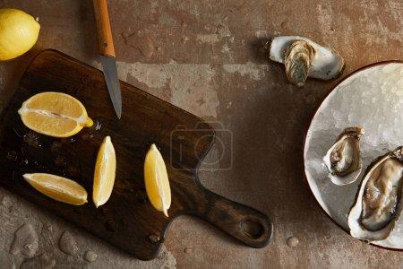 Foto de Vista superior de los limones frescos en la tabla de corte cerca de ostras en el tazón con cubos de hielo. - Imagen libre de derechos