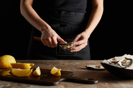 Photo for Cropped view of chef holding knife while opening oyster near lemons on cutting board isolated on black - Royalty Free Image