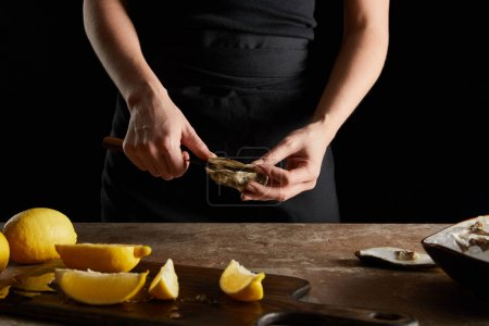 Photo for Cropped view of woman holding knife while opening oyster near lemons on cutting board isolated on black - Royalty Free Image
