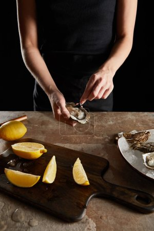 Photo for Cropped view of chef holding fork near fresh oyster isolated on black - Royalty Free Image