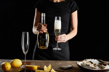 Photo for Cropped view of woman holding glass and bottle with sparkling wine neae oysters in bowl with ice isolated on black - Royalty Free Image