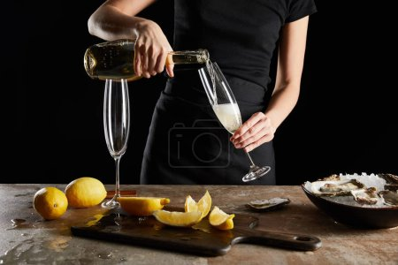Photo for Cropped view of woman pouring sparkling wine in champagne glass near lemons and oysters isolated on black - Royalty Free Image