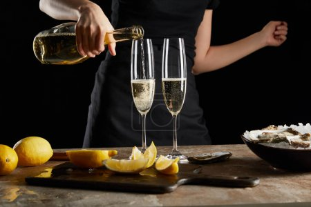 Photo for Cropped view of woman pouring sparkling wine in champagne glass near oysters in bowl with ice isolated on black - Royalty Free Image
