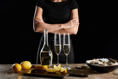 Photo for Cropped view of woman standing with crossed arms near sparkling wine in bottle and oysters in bowl with ice isolated on black - Royalty Free Image