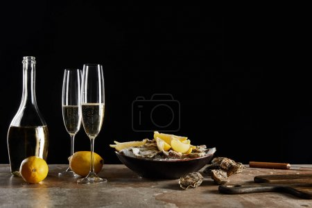 champagne glasses with sparkling wine near oysters and lemons in bowl isolated on black