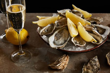 Photo for Champagne glasses with sparkling wine near oysters and fresh lemons in bowl - Royalty Free Image