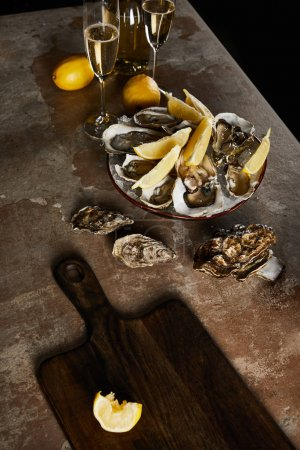 Photo for Champagne glasses with sparkling wine near bottle, oysters and lemons in bowl - Royalty Free Image