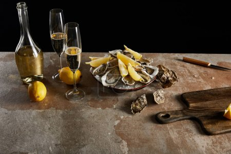 Photo for Champagne glasses with sparkling wine near bottle, oysters and lemons in bowl isolated on black - Royalty Free Image