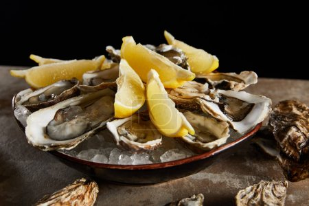 Photo for Close up of oysters and lemons in bowl with ice isolated on black - Royalty Free Image