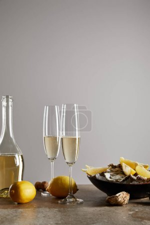 champagne glasses with sparkling wine near bottle, oysters and lemons in bowl isolated on grey