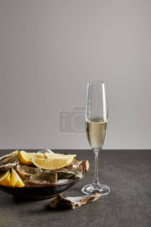 Photo for Delicious oysters and lemons in bowl with ice near champagne glass with sparkling wine isolated on grey - Royalty Free Image