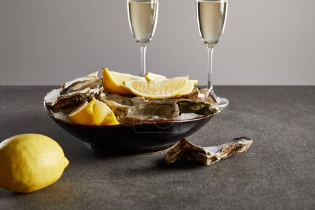 Photo for Selective focus of delicious oysters and lemons in bowl near champagne glasses with sparkling wine isolated on grey - Royalty Free Image