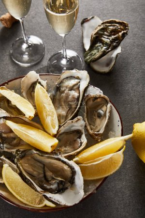Photo for Top view of delicious oysters and lemons in bowl near champagne glasses with sparkling wine on grey surface - Royalty Free Image
