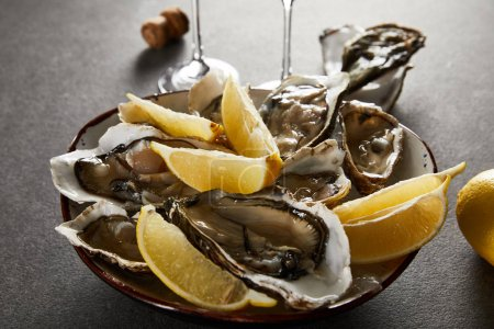 Photo for Selective focus of tasty oysters and lemons in bowl with ice on grey surface - Royalty Free Image
