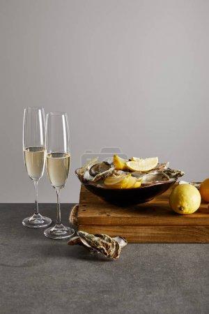 Photo pour Délicieuses huîtres et citrons dans un bol près de verres à champagne avec vin mousseux isolé sur gris - image libre de droit