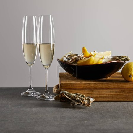 Photo for Fresh oysters and lemons in bowl near champagne glasses with sparkling wine isolated on grey - Royalty Free Image
