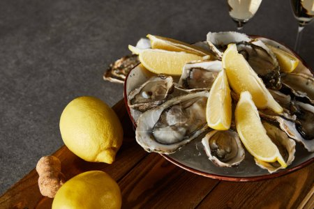 Photo for Selective focus of whole lemons near oysters in bowl and champagne glasses on grey surface - Royalty Free Image