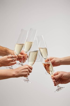 Photo for Cropped view of men and women toasting champagne glasses with sparkling wine isolated on grey - Royalty Free Image