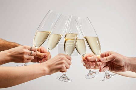 Photo for Cropped view of men and women clinking champagne glasses with sparkling wine isolated on grey - Royalty Free Image