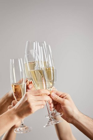 Photo for Cropped view of women and men toasting while holding champagne glasses with sparkling wine isolated on grey - Royalty Free Image