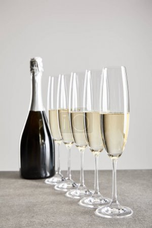 Photo for Selective focus of sparkling wine in champagne glasses near bottle on surface isolated on grey - Royalty Free Image