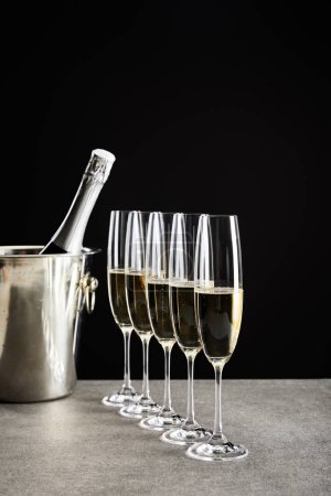 Photo for Selective focus of champagne glasses with sparkling wine near bottle in ice bucket isolated on black - Royalty Free Image