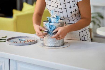 Photo pour Vue partielle du gâteau de décoration de confiseur sur la table de cuisine - image libre de droit