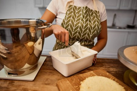 Photo pour Partial view of confectioner taking cream from container for cooking cake - image libre de droit
