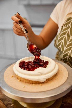 Photo pour Vue agrandie d'un confiseur mettant de la confiture de baies sur un gâteau avec de la crème - image libre de droit