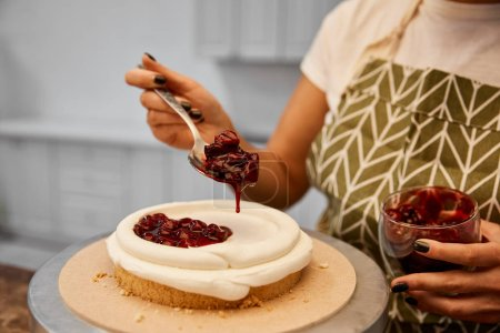 Photo for Cropped view of confectioner adding tasty berry jam on cake - Royalty Free Image