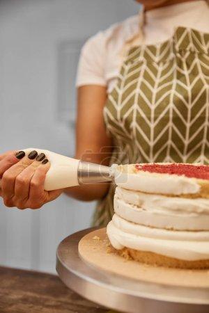 Photo pour Vue croustillante d'un confiseur décorant un biscuit avec de la crème sucrée - image libre de droit