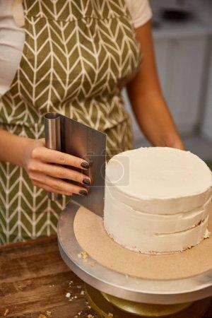Photo pour Vue recadrée du confiseur alignant la crème sucrée sur le gâteau - image libre de droit