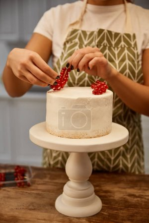Photo for Cropped view of confectioner adding redcurrant on cake - Royalty Free Image