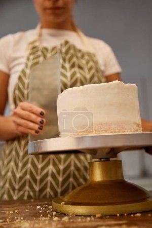 Photo pour Concentration sélective du confiseur alignant la crème sur le gâteau, vue recadrée - image libre de droit
