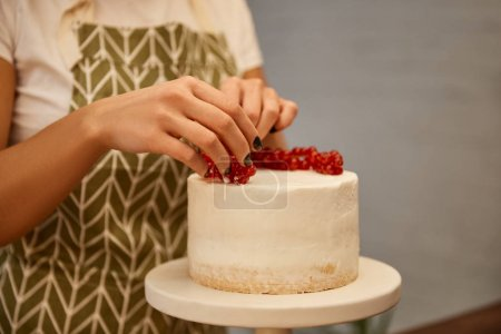 Photo for Cropped view of confectioner adding redcurrant on tasty cake with cream - Royalty Free Image