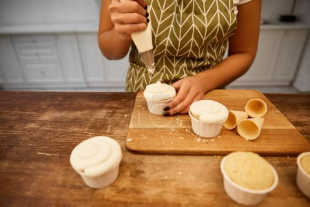 Photo pour Cropped view of confectioner pouring cream on cupcakes beside waffle cones on cutting board - image libre de droit