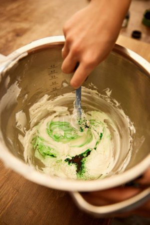 Photo for Cropped view of confectioner mixing cream with green food coloring in bowl - Royalty Free Image