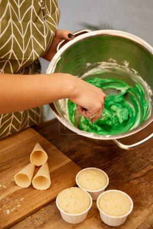 abgeschnittene Ansicht eines Konditors, der süße Sahne neben Cupcakes und Waffelkegeln auf dem Tisch mixt