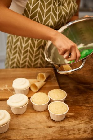 Photo for Cropped view of confectioner mixing cream for cupcakes and waffle cones on table - Royalty Free Image