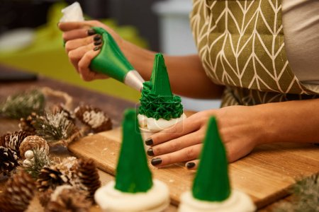 Photo for Selective focus of confectioner decorating tasty Christmas tree cupcakes beside spruce cones on table, cropped view - Royalty Free Image