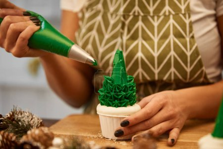 Photo for Cropped view of confectioner adding green cream on Christmas tree cupcake beside spruce cones on table - Royalty Free Image