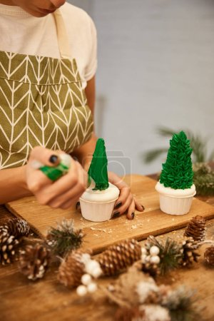 Photo for Cropped view of confectioner using pastry bag with cream on Christmas tree cupcakes beside spruce cones on table - Royalty Free Image