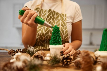 Photo pour Cropped view of confectioner decorating Christmas tree cupcake with green cream beside spruce cones on table - image libre de droit
