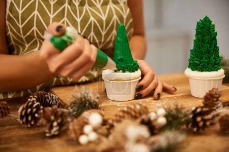 Photo pour Vue recadrée de confiseur faisant des cupcakes d'arbre de Noël avec de la crème verte avec des cônes d'épinette sur la table - image libre de droit