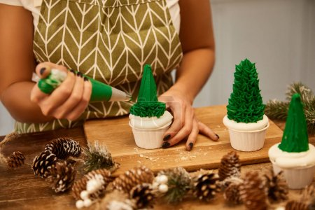 Photo for Cropped view of confectioner making Christmas tree cupcakes with green sweet cream beside spruce cones on table - Royalty Free Image